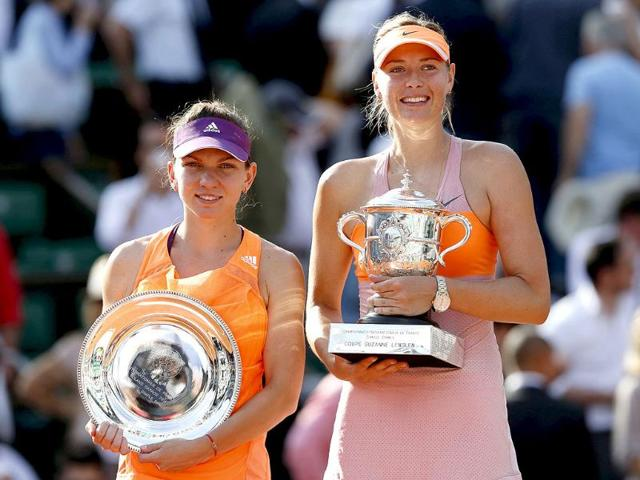 Maria Sharapova of Russia (R) poses with Simona Halep of Romania (L) during the trophy ceremony after winning their women