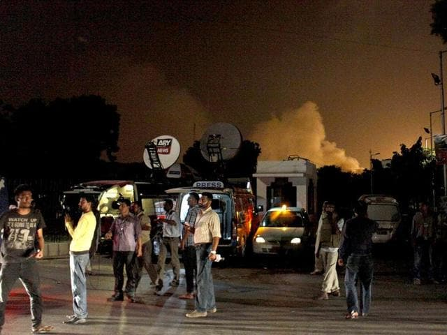 Reporters stand outside Karachi airport terminal building where security forces are fought with attackers in Pakistan. (AP Photo/Shakil Adil)