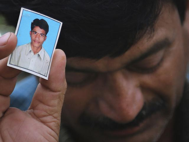 Bonath Shekar Naik shows a portrait of his son Rambabu, only one name available, one of the 24 students feared dead during a field trip near Manali, at the college premises of VNR Vignana Jyothi Institute of Engineering and Technology, on the outskirts of Hyderabad. (AP Photo)