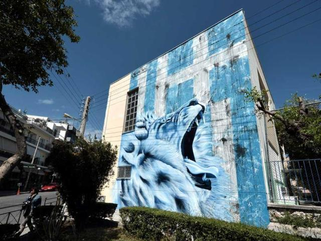 A-giant-lion-roars-before-a-frayed-Greek-flag-on-a-graffiti-by-BANE-on-a-wall-of-a-primary-school-in-Athens-suburb-of-Nikaia-AFP-photo