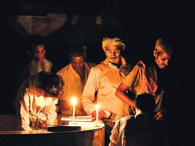 People-work-in-the-light-of-candles-near-a-sulabh-sauchalaya-after-power-cut-in-Old-Delhi-Arun-Sharma-HT-photo