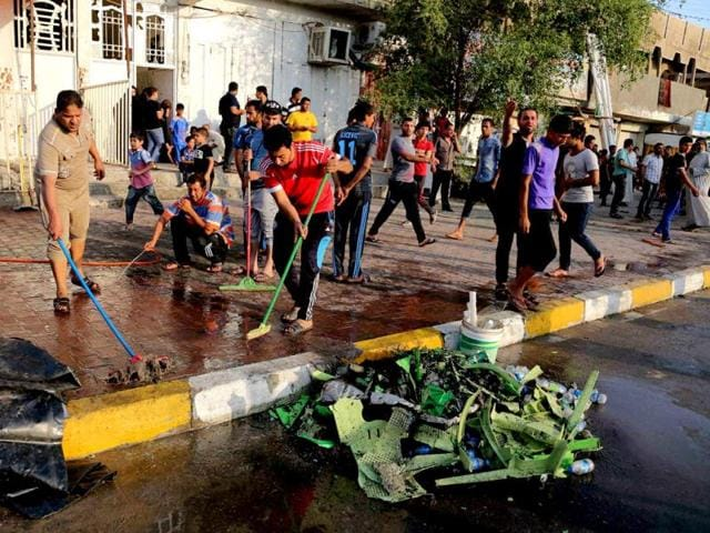 People clean up in the aftermath of a suicide bomb attack in Baghdad