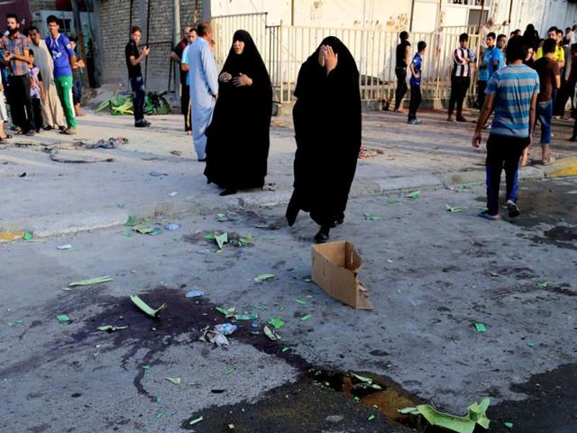 Civilians inspect the aftermath of a suicide bomb attack in Baghdad