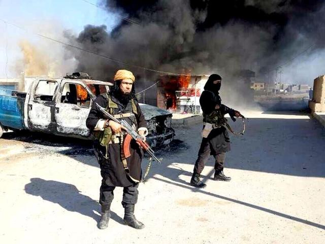 Shakir-Waheib-a-senior-member-of-the-al-Qaida-breakaway-group-Islamic-State-of-Iraq-and-the-Levant-ISIL-left-next-to-a-burning-police-vehicle-in-Iraq-s-Anbar-Province-AP-Photo
