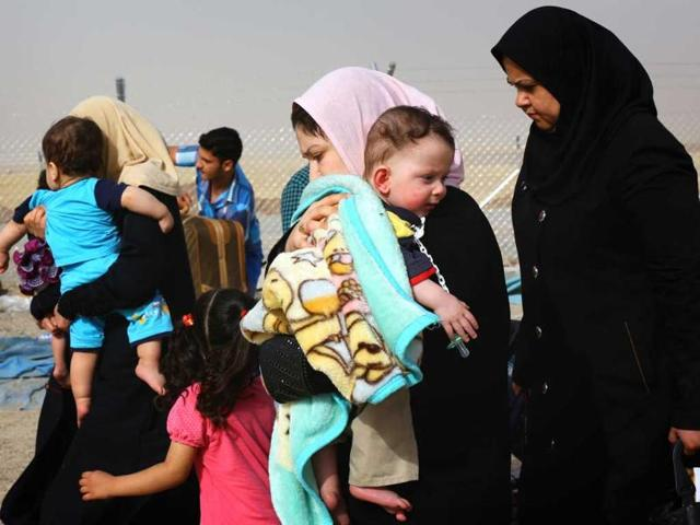 Families fleeing the violence in the Iraqi city of Mosul arrive at a checkpoint on the outskirts of Arbil, in Iraq