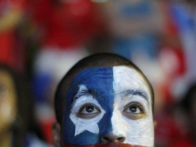 A soccer fan with his face painted to represent the Chilean national flag, watches the live broadcast of the match between Chile and Australia.(AP Photo)