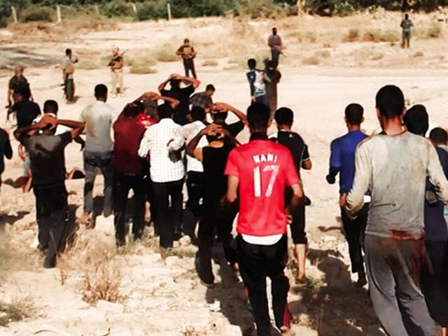 This image posted on a militant website on Saturday, which has been verified and is consistent with other AP reporting, appears to show militants from the al Qaeda-inspired Islamic State of Iraq and the Levant (ISIL) leading captured Iraqi soldiers wearing plain clothes to an open field moments before shooting them in Tikrit, Iraq. (AP Photo via militant website)