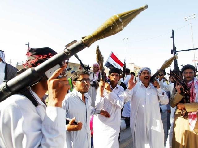 Tribal fighters shout slogans as they carry weapons during a parade on the streets of Najaf, south of Baghdad. (Reuters Photo)