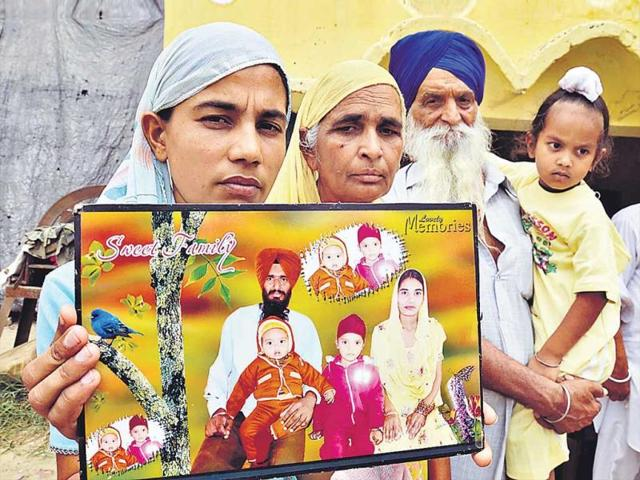 Jalal-Usma-village-resident-Harjit-Kaur-holding-a-picture-of-her-husband-Gurcharan-Singh-who-is-missing-in-Iraq-since-June-2014-HT-File-Photo