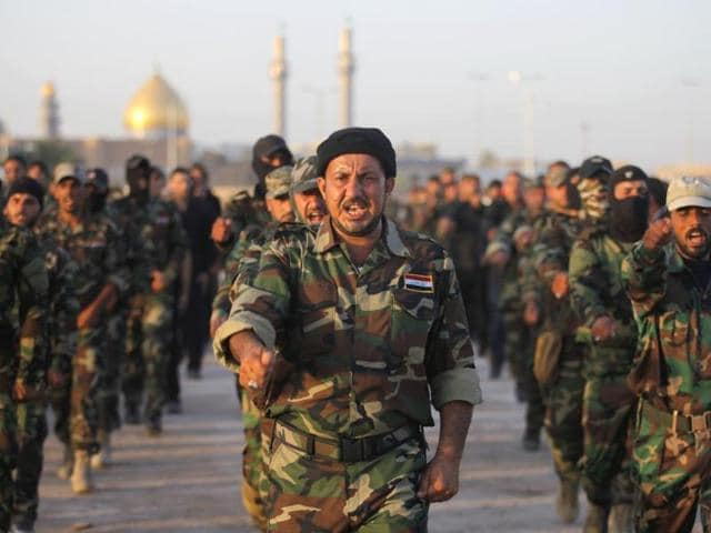 Volunteers-in-the-newly-formed-Peace-Brigades-participate-in-a-parade-near-the-Imam-Ali-shrine-in-the-southern-holy-Shiite-city-of-Najaf-AP-Photo