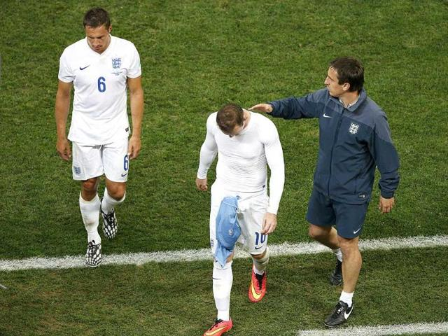 England-s-Wayne-Rooney-C-is-comforted-by-deputy-coach-Gary-Neville-R-as-he-walks-off-the-field-with-teammate-Phil-Jagielka-after-losing-to-Uruguay-in-their-World-Cup-Group-D-match-at-the-Corinthians-arena-in-Sao-Paulo-Reuters-Photo