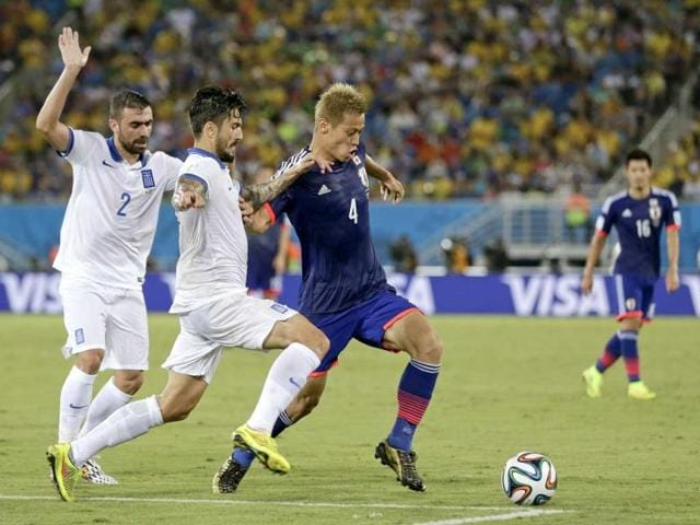 Japan-s-Keisuke-Honda-R-takes-on-the-Greek-defence-during-the-Group-C-World-Cup-match-between-Japan-and-Greece-at-the-Arena-das-Dunas-in-Natal-Brazil-AP-Photo