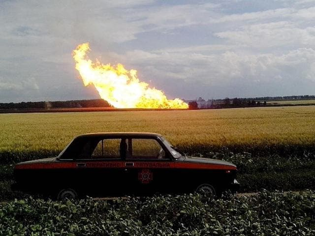 Ukraine-Iskivtsi-June-17-2014-This-handout-picture-taken-and-released-by-the-Ukrainian-Emergency-Service-shows-a-police-car-parked-beside-a-field-near-a-fire-on-the-gas-pipeline-the-village-of-Iskivtsi-A-blast-hit-a-major-Ukrainian-pipeline-used-to-transport-Russian-natural-gas-to-European-clients-AFP-PHOTO