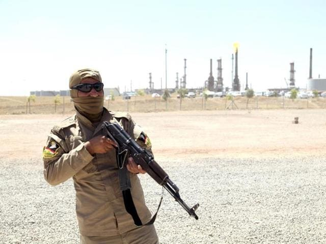 A member of Kurdish security forces takes up position with his weapon as he guards an oil refinery on the outskirts of Mosul. (Reuters photo)