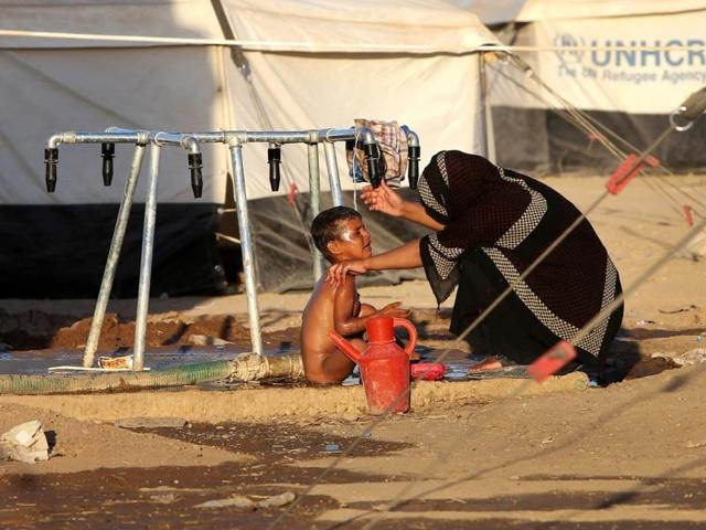 An Iraqi woman bathes her son at a camp for displaced Iraqis who fled from Mosul and other towns following attacks by Sunni insurgents. (AP photo)