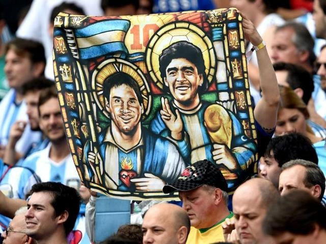 An-Argentine-fan-holds-an-image-of-Lionel-Messi-and-former-footballer-Diego-Maradona-depicted-as-saints-during-their-World-Cup-Group-F-match-against-Nigeria-at-the-Beira-Rio-Stadium-in-Porto-Alegre-AFP-Photo