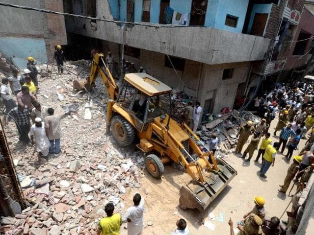 Bulldozer-clears-the-debris-while-locals-look-at-the-collapsed-three-storey-residential-building-in-Tulsi-Nagar-area-of-Inderlok-New-Delhi-PTI-photo
