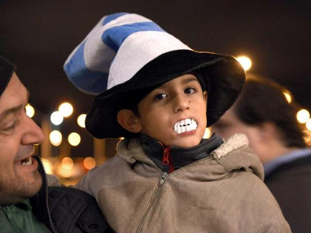 A-child-shows-his-support-for-Uruguay-player-Luis-Suarez-by-wearing-toy-plastic-vampire-s-teeth-AP-Photo