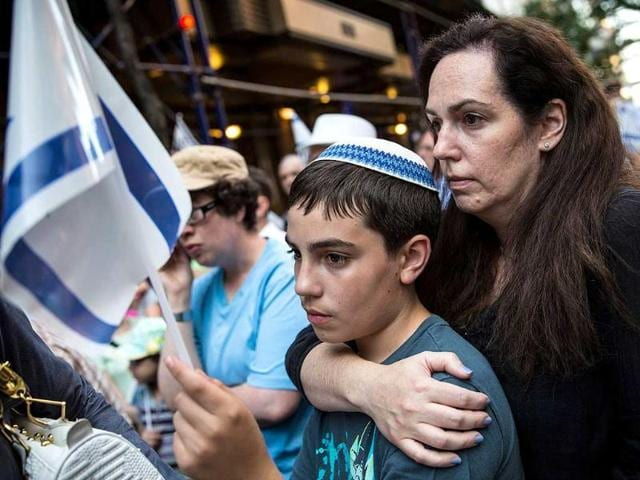 Deborah Yasinsky and her son Aryeh Kalb, age 13, attend a vigil in remembrance of three Israeli boys who went missing earlier this month in New York City. On Tuesday, the Israeli army announced that they had found three bodies, which they believe are the missing teenagers. The boys went missing more than two weeks ago in the West Bank.  (Getty Images/AFP)