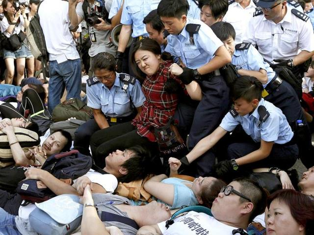 A-protester-reacts-as-she-is-dragged-away-by-policewomen-on-a-street-outside-HSBC-headquarters-at-Hong-Kong-s-financial-Central-district-after-staying-an-overnight-sit-in-with-fellow-demonstrators-Reuters-Photo