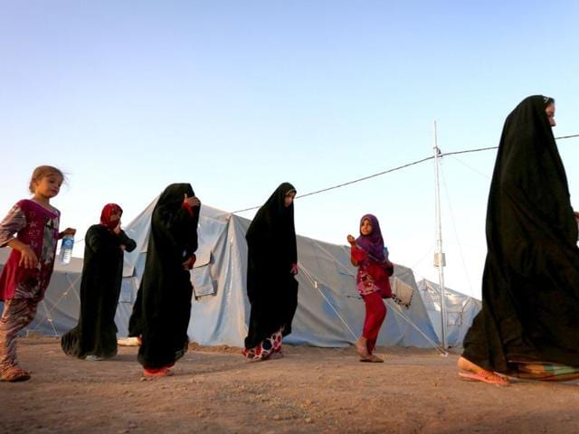 Displaced Iraqi woman walk at sunset past tents provided by the UN refugee agency at a temporary camp set up to shelter people fleeing violence in northern Iraq in Aski Kalak, 40 kms west of the Kurdish autonomous region