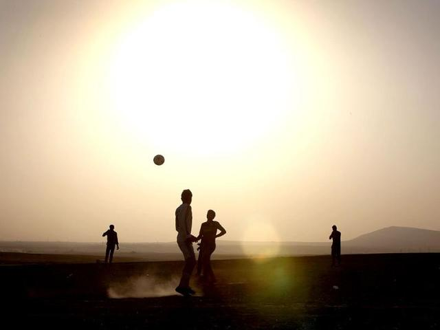 Displaced Iraqis play football at sunset at a temporary camp set up by the UN refugee agency to shelter people fleeing violence in northern Iraq in Aski Kalak, 40 kms west of the Kurdish autonomous region