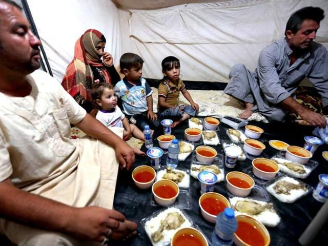 Displaced Iraqis ready to break their fast during the holy Muslim month of Ramadan, as they sit in a tent provided by the UN refugee agency at a temporary camp set up to shelter people fleeing violence in northern Iraq in Aski kalak, 40 kms west of the Kurdish autonomous region