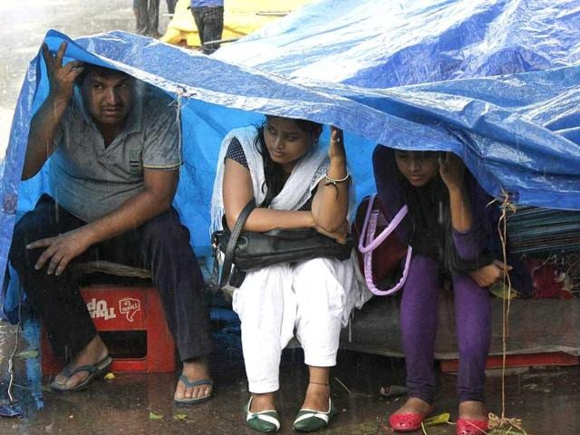 People-take-shade-while-it-rains-in-Janpath-New-Delhi-Srishti-Sethi-HT-Photo