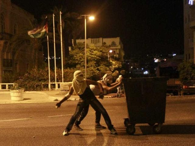 Palestinian-protesters-shield-themselves-behind-a-garbage-container-as-they-hurl-stones-toward-an-Israeli-military-observation-tower-at-a-section-of-the-separation-barrier-to-the-main-entrance-of-the-West-Bank-city-of-Bethlehem-after-the-abduction-and-killing-of-a-Palestinian-teen-by-suspected-Jewish-settlers-AFP-photo