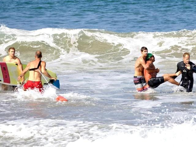 Two-men-carry-a-swimmer-second-from-right-after-he-was-bitten-by-a-great-white-shark-as-lifeguards-close-in-at-left-in-the-ocean-off-Southern-California-s-Manhattan-Beach-AP-photo-goofyfootphotography-com-Laura-Joyce