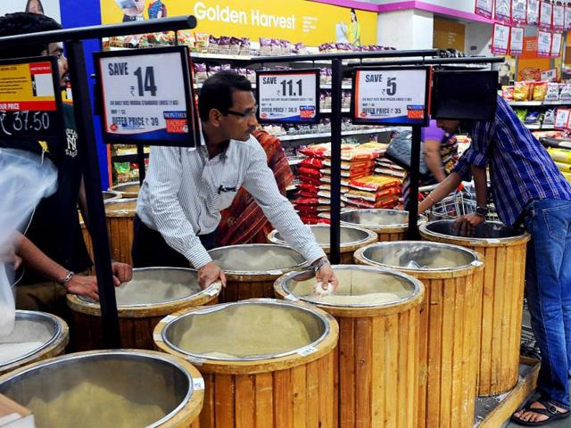 A-shopper-looks-at-prices-as-he-inspects-the-quality-of-rice-for-sale-at-a-supermarket-in-Mumbai-AFP-photo