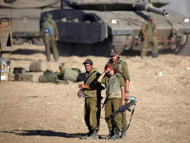 Israeli soldiers walk next to tanks stationed on a field outside the central Gaza Strip (Reuters photo)