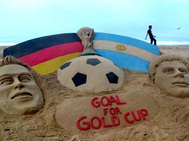 An-football-fan-kicks-a-ball-behind-a-sand-sculpture-of-the-Fifa-World-Cup-trophy-between-the-German-left-and-Argentina-flags-alongside-the-finalist-captains-Philipp-Lahm-left-and-Lionel-Messi-created-by-sand-artist-Sudarsan-Pattnaik-at-Puri-beach-AFP-Photo