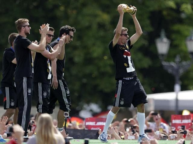 Thomas Mueller, Mats Hummels, Erik Durm and Christoph Kramer, from left, celebrate with the trophy after the arrival of the German national soccer team in Berlin on July 15, 2014. (AP Photo/Petr David Josek)