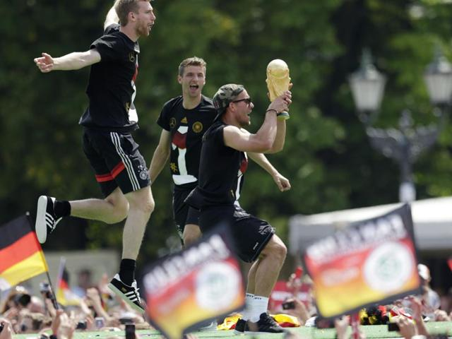 Lukas Podolski holds the trophy during a fan party after the arrival of the German national soccer team in Berlin on July 15, 2014. (AP Photo/Petr David Josek)