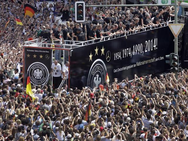 Members of the German soccer squad wave to fans after the arrival of the German national soccer team in Berlin. Germany's World Cup-winning team has returned home from Brazil to celebrate the country's fourth title with huge crowds of fans. (AP Photo/Michael Sohn)