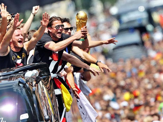 "Players of the German national soccer team celebrate on a truck during their return to Berlin, Tuesday July 15, 2014. An estimated 400,000 people packed the ""fan mile"" in front of the Berlin landmark to welcome home coach Joachim Loew"