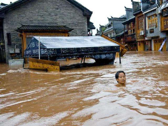 This-picture-shows-a-woman-making-her-way-through-floodwaters-in-the-ancient-town-of-Fenghuang-central-China-s-Hunan-province-AFP-Photo