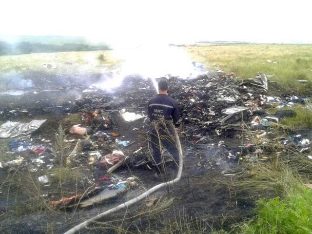 A-man-works-at-putting-out-a-fire-at-the-site-of-a-Malaysia-Airlines-Boeing-777-plane-crash-in-the-settlement-of-Grabovo-in-the-Donetsk-region-Reuters-photo