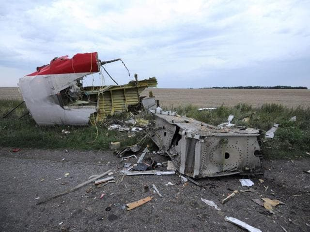 An-armed-separatist-guards-in-front-of-wagons-containing-the-remains-of-victims-from-the-downed-Malaysia-Airlines-Flight-MH17-at-a-railway-station-in-the-eastern-Ukrainian-town-of-Torez-AFP-Photo