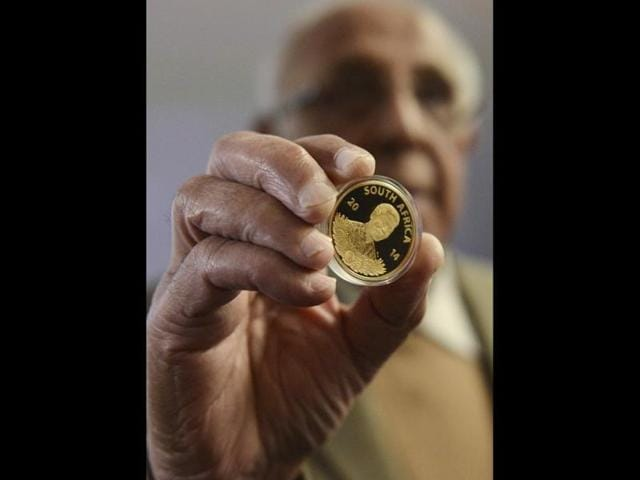 Former-political-prisoner-Ahmed-Kathrada-holds-a-24-carat-gold-coin-honouring-former-president-Nelson-Mandela-at-the-South-African-Reserve-Bank-in-Pretoria-South-Africa-launched-a-set-of-limited-edition-gold-and-silver-coins-on-Friday-to-honour-Mandela-on-what-would-have-been-the-late-anti-apartheid-hero-s-96th-birthday-Reuters-Photo