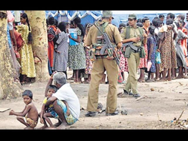 Sri-Lankan-soldiers-stand-guard-as-Tamil-civilians-queue-to-receive-food-at-a-refugee-camp-in-May-2009-AFP-Photo