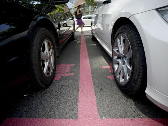 In-this-photo-a-woman-passes-cars-parked-in-pink-marked-out-spaces-in-front-of-the-Dashijiedaduhui-or-World-Metropolis-centre-in-the-seaport-city-of-Dalian-northeast-China-s-Liaoning-province-AFP-Photo
