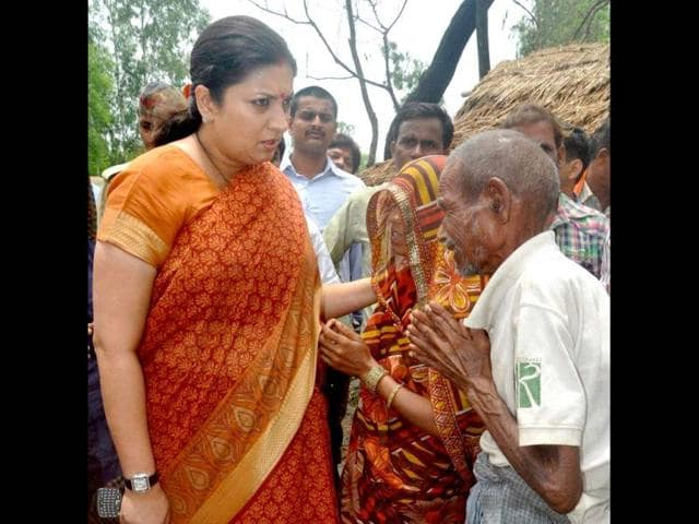 HRD-minister-Smriti-Irani-consoling-villagers-during-a-visit-to-the-fire-hit-Barauliya-village-in-Amethi-PTI-photo