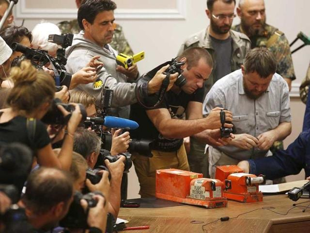 Members-of-the-media-take-pictures-of-black-boxes-belonging-to-Malaysia-Airlines-flight-MH17-before-their-handover-from-Ukrainian-pro-Russian-separatist-to-Malaysian-representatives-in-Donetsk-Reuters