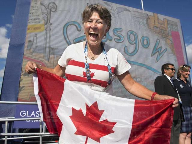 Trap shooter Susan Nattrass smiles as she display the Canadian flag as members of the Canadian team attend their welcome ceremony at the Commonwealth Games in Glasgow. AP Photo