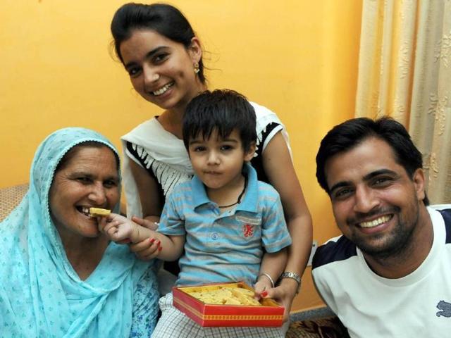 Gurvash-2-son-of-Rajwinder-Kaur--offering-sweets--to-his-grandmother-Sukhbir-Kaur-mother-of-Rajwinder-along-with-his-father-Kuljinder-Singh-at-their-residence-in-Jalandhar-on-Sunday-Pardeep-Pandit-HT