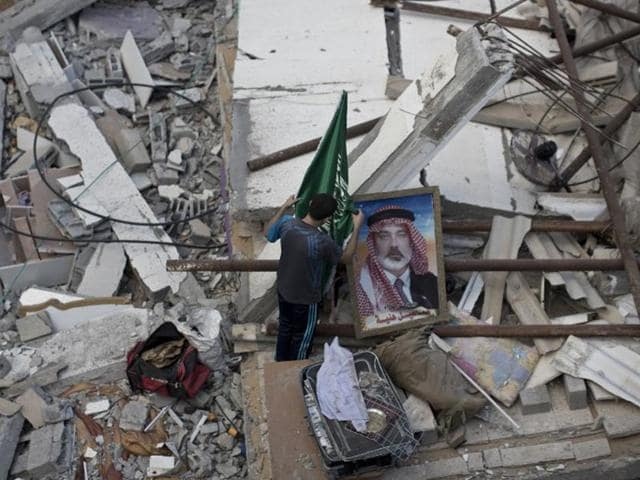 A Palestinian man displays an Islamist Hamas movement flag and a portrait of Hamas top leader in Gaza, Ismail Haniya, on the rubble of the latter