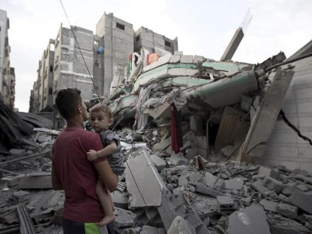 A Palestinian man carrying a child looks at the destroyed house of Hamas top leader Ismail Haniya, after it was hit by an overnight Israeli air strike on July 29, 2014 in Gaza City. (AFP/Mahmud Hams)