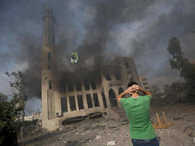 A Palestinian man reacts in front of a destroyed mosque after it was hit by an Israeli air strike on July 29, 2014. Bloodshed in and around Gaza surged with strikes killing at least 13 Palestinians, a day after five Israeli soldiers died, shattering hopes for an end to three weeks of violence. (AFP/Mahmud Hams)